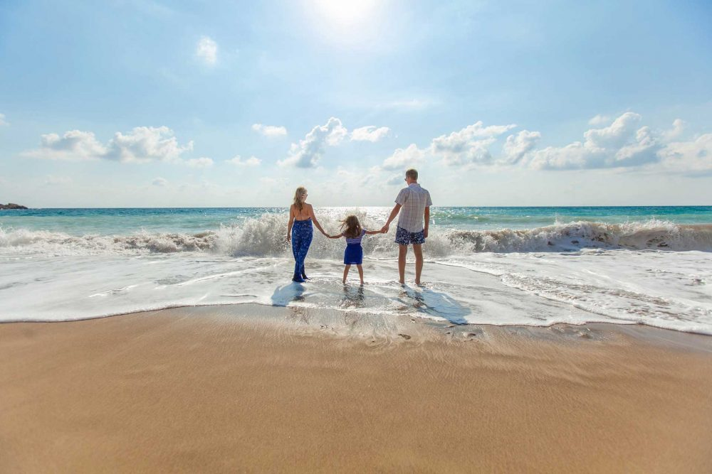 family on beach thinking about life risk sales